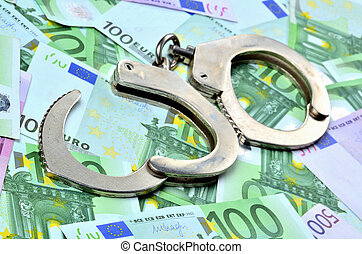Close-up of police handcuffs on euro banknotes - corruption concept