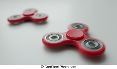 Close up of popular toy fidget spinner rotating over white background