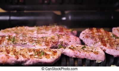 Close-up of pork production. Pork steak fried on a grill