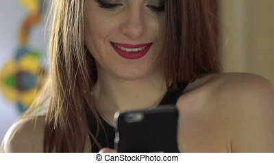 Close up of portrait of girl smiling and looking on the phone. Slow motion