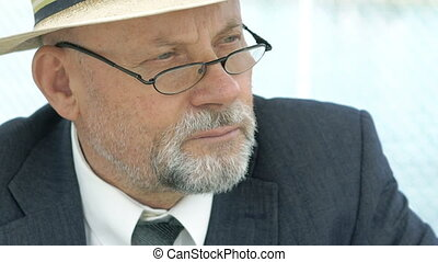 Close up of portrait of old man in hat, suit and glasses looking aside. 4K