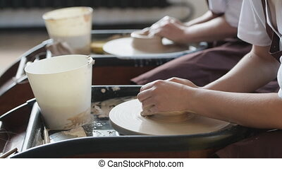 Close up of Potter hands in action shaping raw earthen clay ...