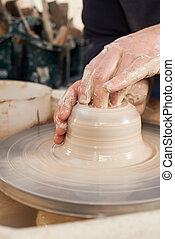 Close Up Of Potter Moulding Clay On Wheel