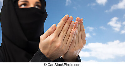 close up of praying muslim woman in hijab over sky -...