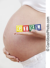 Close Up Of Pregnant Woman Holding Blocks Spelling Baby