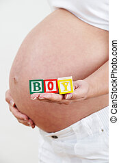 Close Up Of Pregnant Woman Holding Blocks Spelling BOY