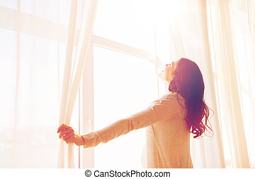 close up of pregnant woman opening window curtains -...