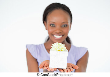 Close up of present being held by smiling woman against a white background