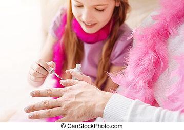 Close up of pretty girl polishing nails