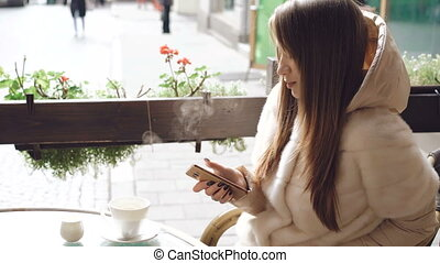 Close up of pretty girl using phone in cafe when coffee is steaming 4K