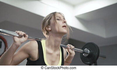 Close up of pretty girl working out squats with heavy barbell in the gym in 4K