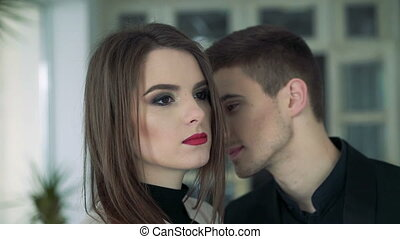 Close up of pretty girl's face. Boy kissing in neck. Happy. Slowly