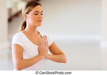woman doing yoga meditation - close up of pretty woman doing...
