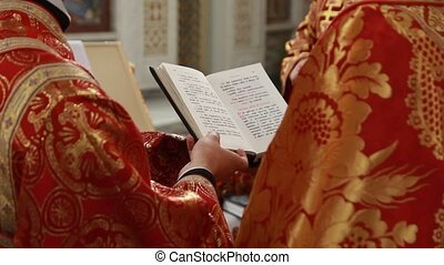 Close up of priest reading the holy bible with rosary