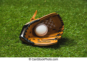 close up of professional baseball glove with ball on green grass