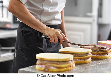 Close up of professional confectioner making a delicious cake in the pastry shop.