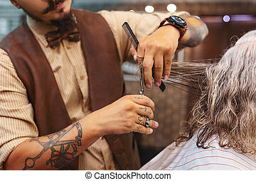 Close up of professional hairdresser that doing haircutting