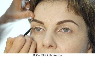 Close-up of professional make-up artist applying eyeliner on...