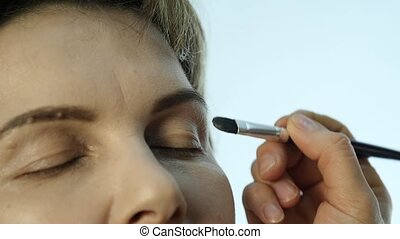 Close-up of professional make-up artist applying eyeliner on...