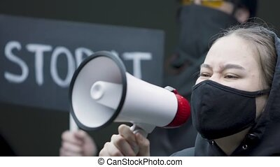 Close up of protesting young woman in black mask screaming through megaphone while being on anti-racism protest. High quality 4k footage