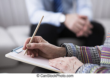 Close-up of psychotherapist writing notes