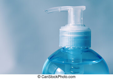 Close-up of pump bottle head. Alcohol gel or hand sanitizer. Protection against Coronavirus (COVID-19). Isolated on blue background. Copy space.