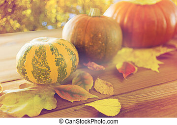 close up of pumpkins on wooden table outdoors