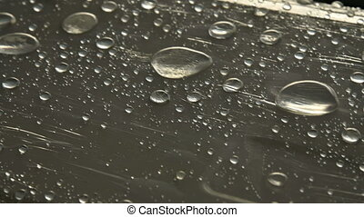 Close-up of raindrops of different sizes on the surface...