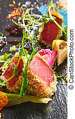 Close up of rare seared Ahi tuna slices with fresh vegetable salad on a plate.