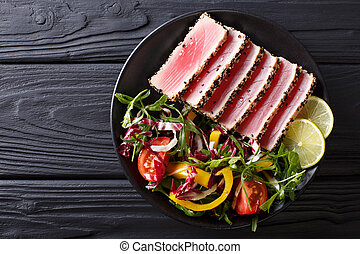 Close up of rare seared Ahi tuna slices with fresh vegetable salad. Top view horizontal