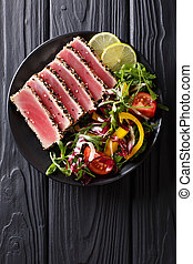 Close up of rare seared Ahi tuna slices with fresh vegetable salad. Top view vertical