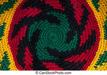 Close up of rastafarian hat with dreads - handmade knitting isolated on white background
