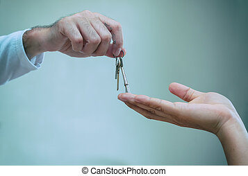 Close up of realtor hand giving house key to owner home, buying selling property business.