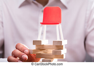Close-up Of Red Chair Over Stacked Wooden Blocks
