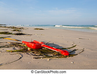 Close up of red childs spade on sandy beach