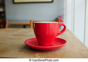 close up of red color coffee mug on table at cafe