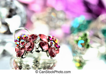 Close-up of red flower shaped earrings with red diamonds and ring jewelery - reflection effect - colored backgrounds - purple - warm color balance