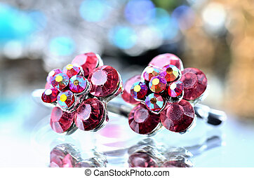 Close-up of red flower shaped earrings with red diamonds jewels - reflection effect - colored backgrounds - blue