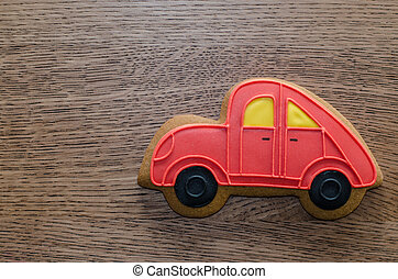 Close-up of red gingerbread car lying on the wooden table background