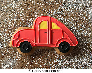 Close-up of red gingerbread car lying on the wooden table with sugar powder background