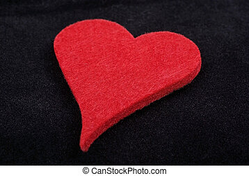 Close up of red heart isolated on black velvet background. Studio shot.