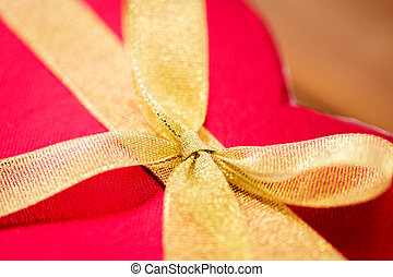 close up of red heart shaped gift box with bow