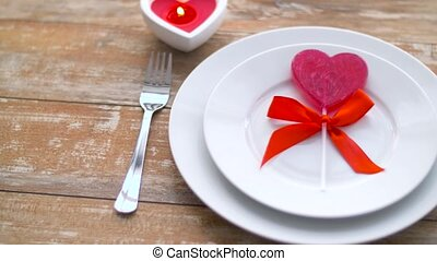 close up of red heart shaped lollipop on plate - st...