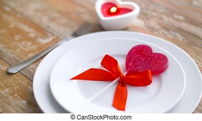 close up of red heart shaped lollipop on plate - valentines...