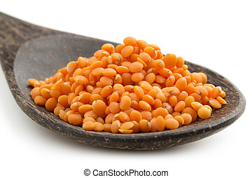 close up of red lentils in a wooden spoon