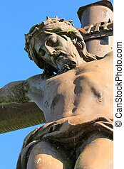 Jesus Christ on the cross - Close up of red metallic outdoor...