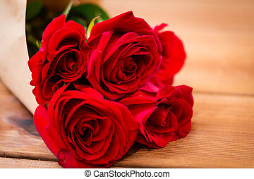 close up of red roses bunch wrapped into paper