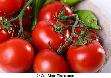 Close up of red tomatoes and green peperoni on white ...