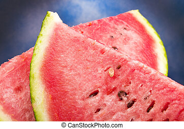 Close-up of red watermelon against the blue sky