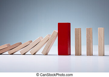 Red Wooden Block Amidst Falling And Upright Domino Pieces